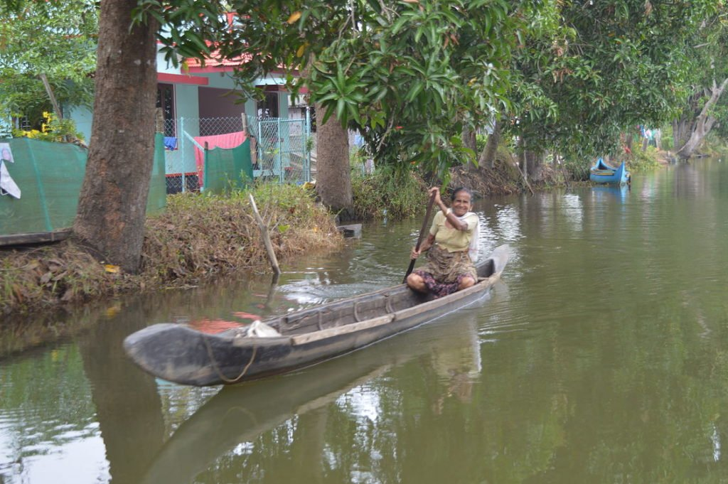 An old lady travelling by small rice boat